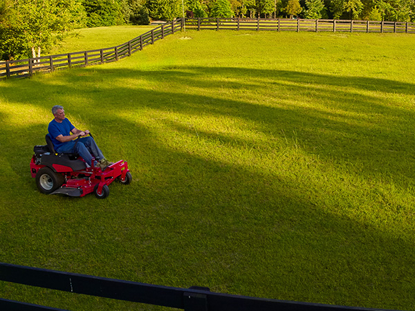 Man cutting grass on zero turn mower in field